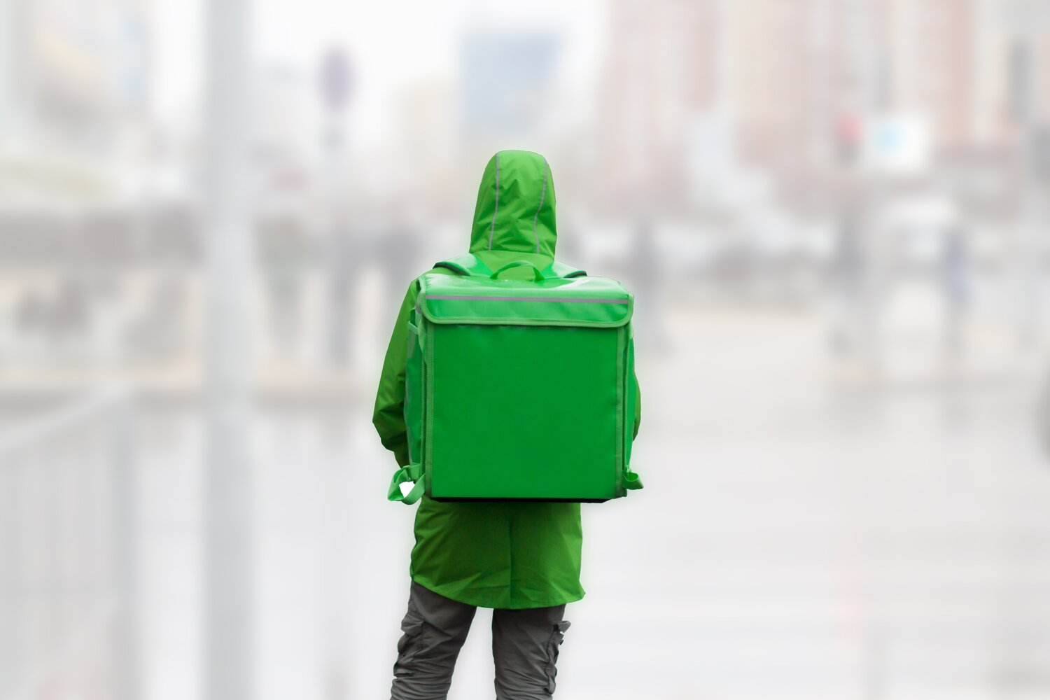 unrecognizable-young-man-courier-in-green-jacket-with-green-backpack-on-a-background-of-blurred_t20_8d9bzj